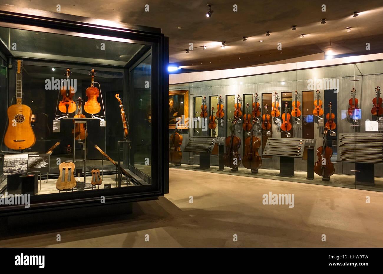 Old violines and guitars on display in Interior musée de la cite, museum, Cite de la musique, Paris, France. - Stock Image
