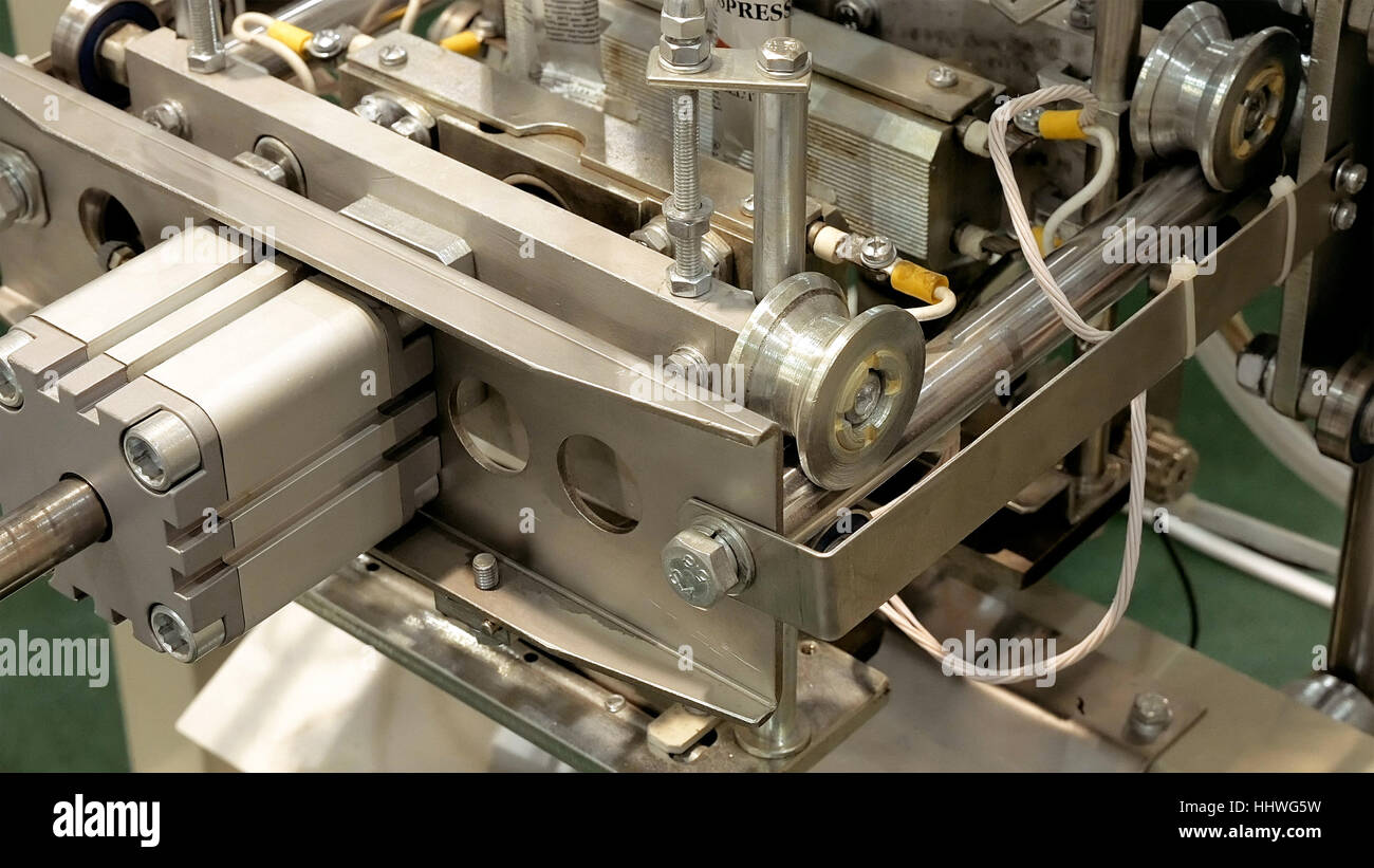 Factory packing machine with pipes and rolls - Stock Image