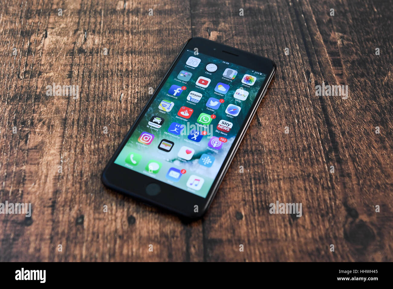 Apple Iphone 7 plus on a wooden surface without hands and people in the shot  IOS 10 - Stock Image