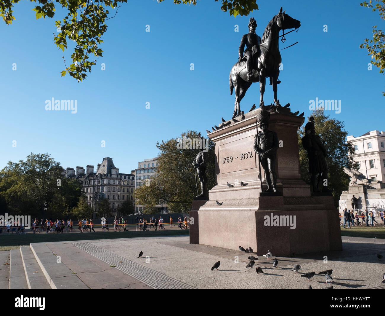 Marathon runners passing by statue of the Duke of Wellington - Stock Image