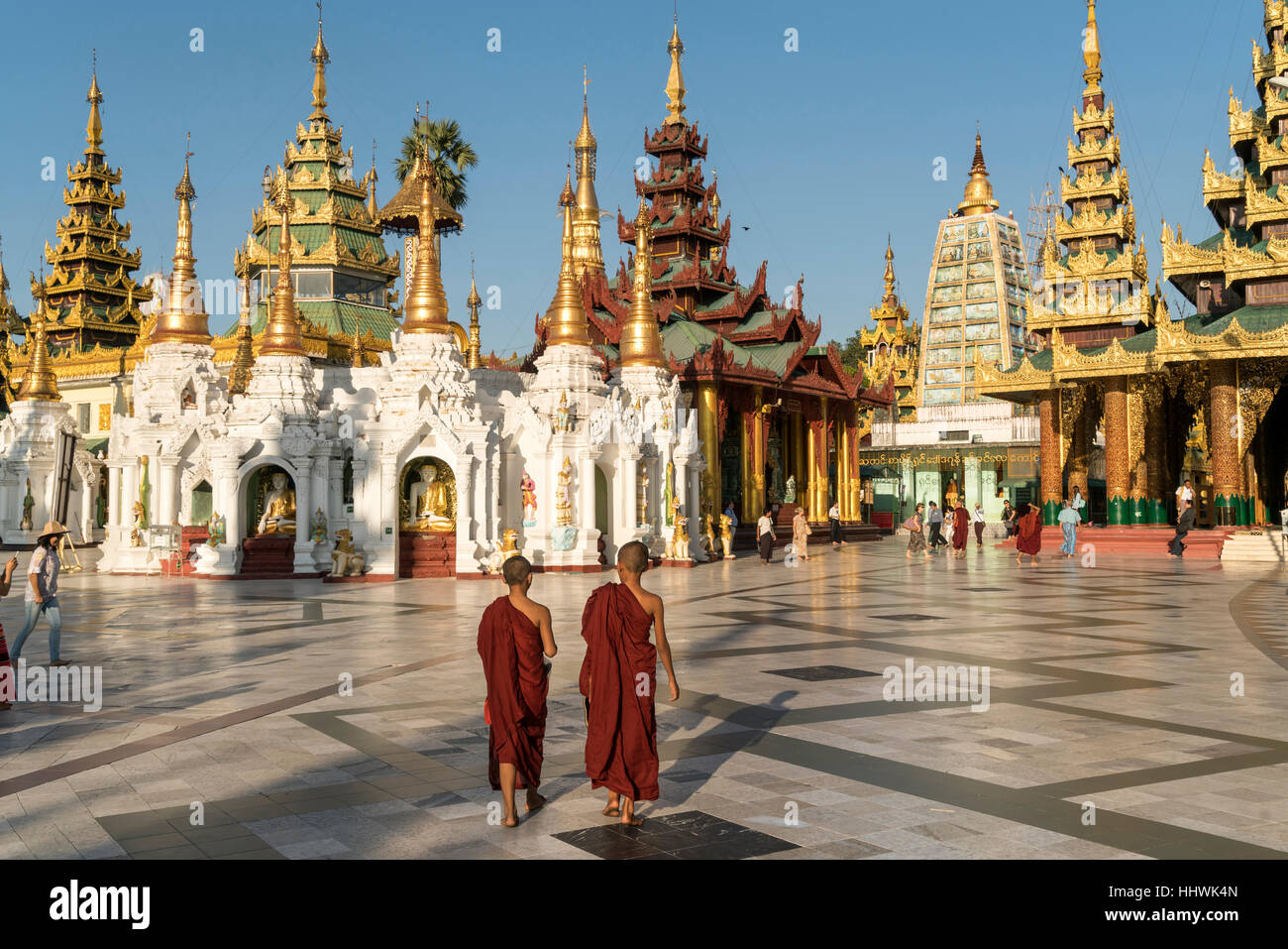 Monks in front of Shwedagon Zedi Daw, Shwedagon Pagoda, Yangon, Myanmar - Stock Image