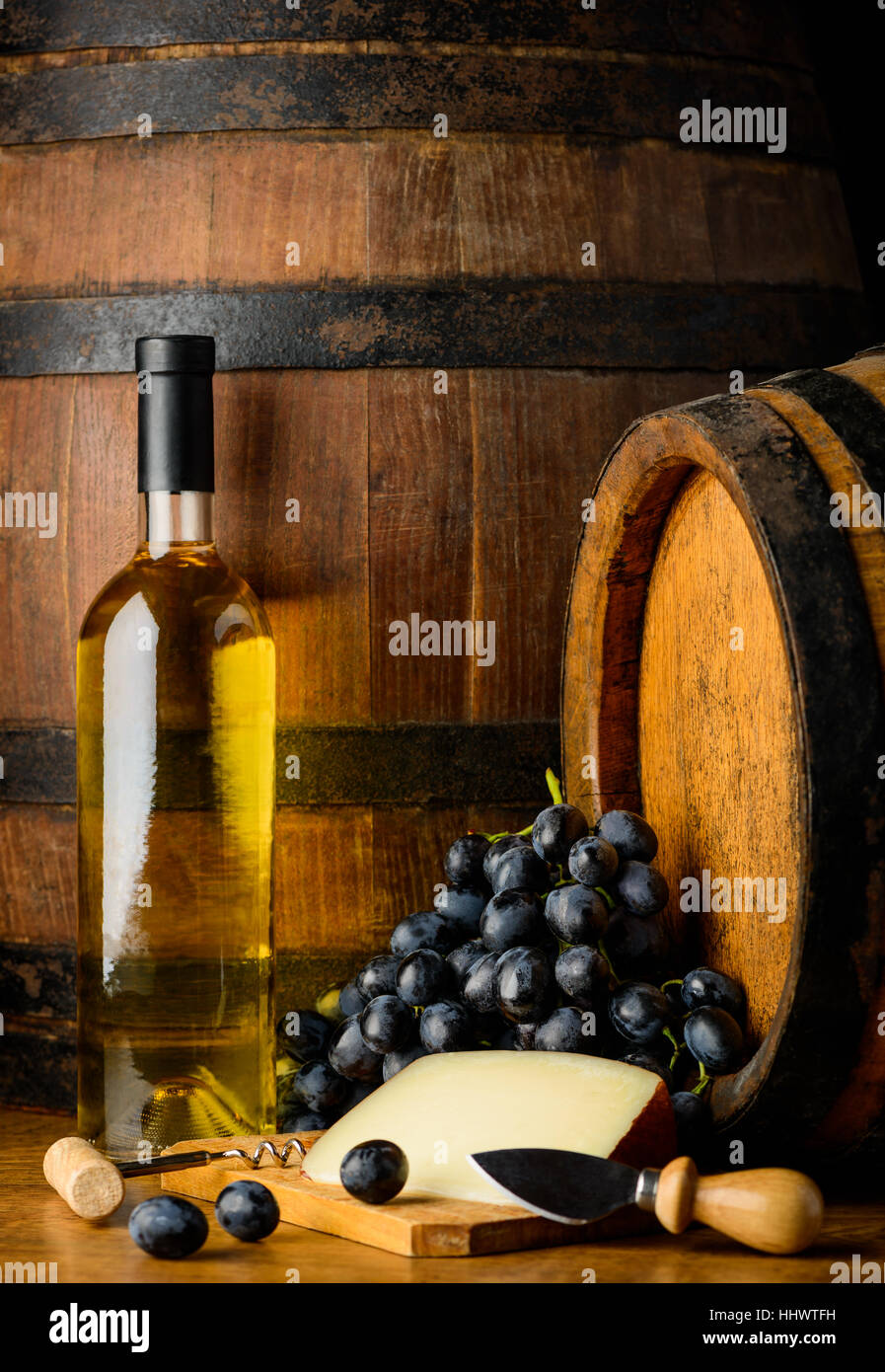 White wine in bottle with dark grapes and chese with wooden background - Stock Image