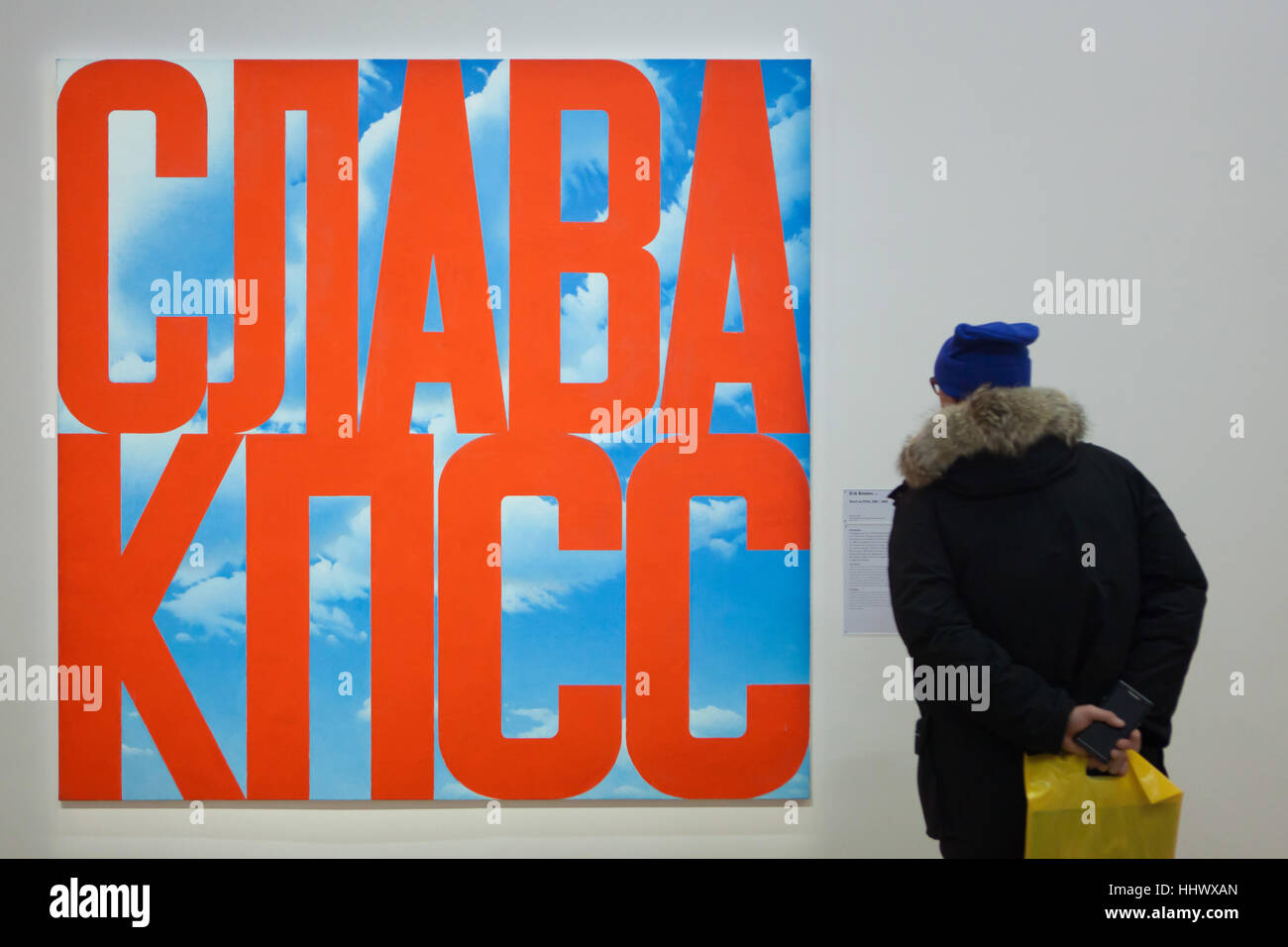 Visitor in front of the panting entitled Glory to the CPSU (2003-2005) by Russian conceptual artist Erik Bulatov - Stock Image