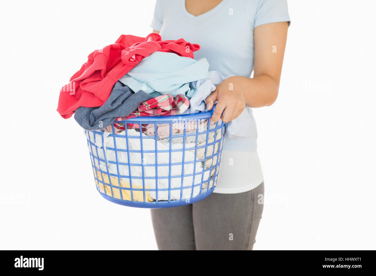Woman holding an overflowing laundry basket - Stock Image