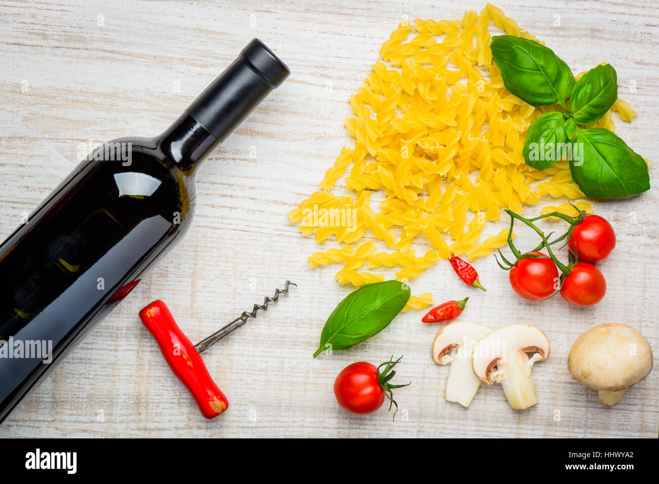 Bottle of red wine with corkscrew and Fusilli doppia rigatura Pasta and fresh vegtables - Stock Image
