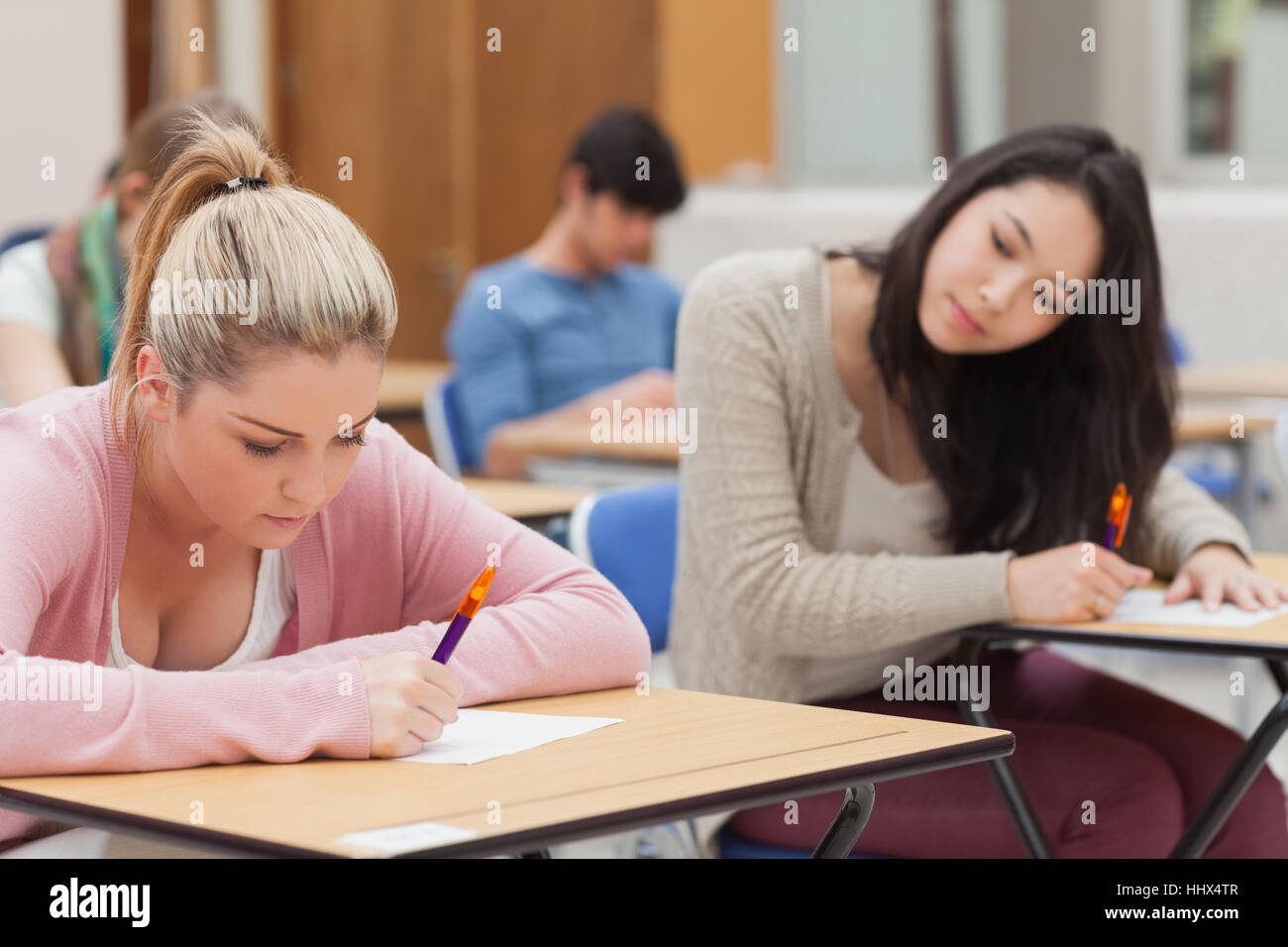 Burnette is trying to copy blonde student in exam in exam hall in college - Stock Image