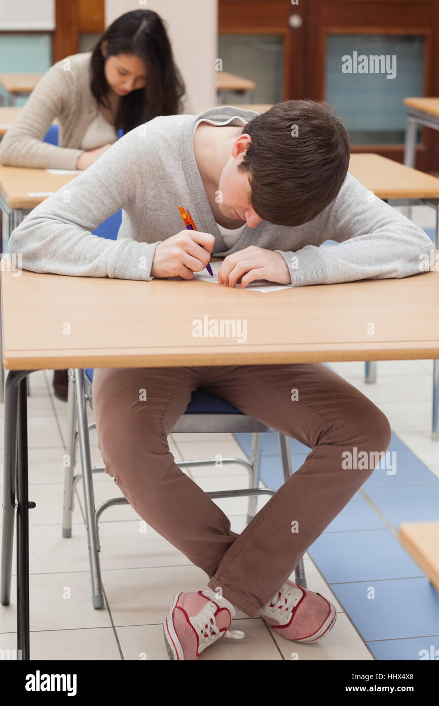 Student writing at desk in classroom - Stock Image