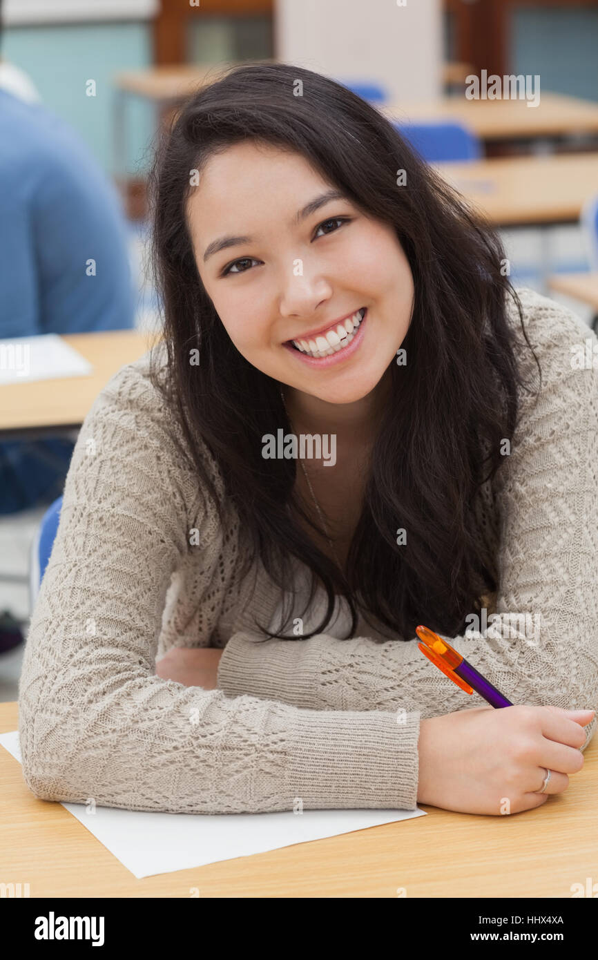 Woman sitting at the table holding a pen while smiling - Stock Image