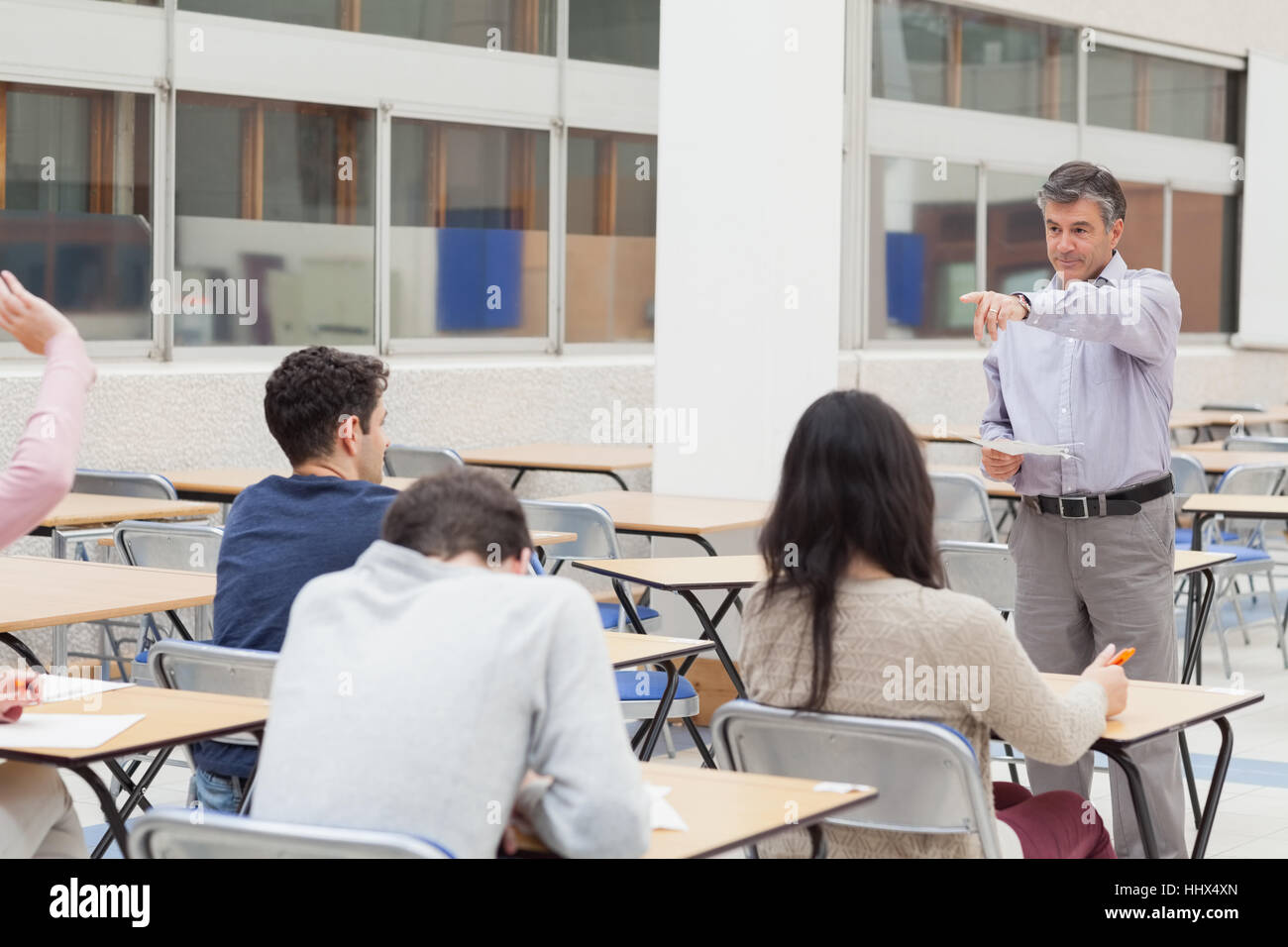 Teacher pointing at student asking question in classroom in college - Stock Image