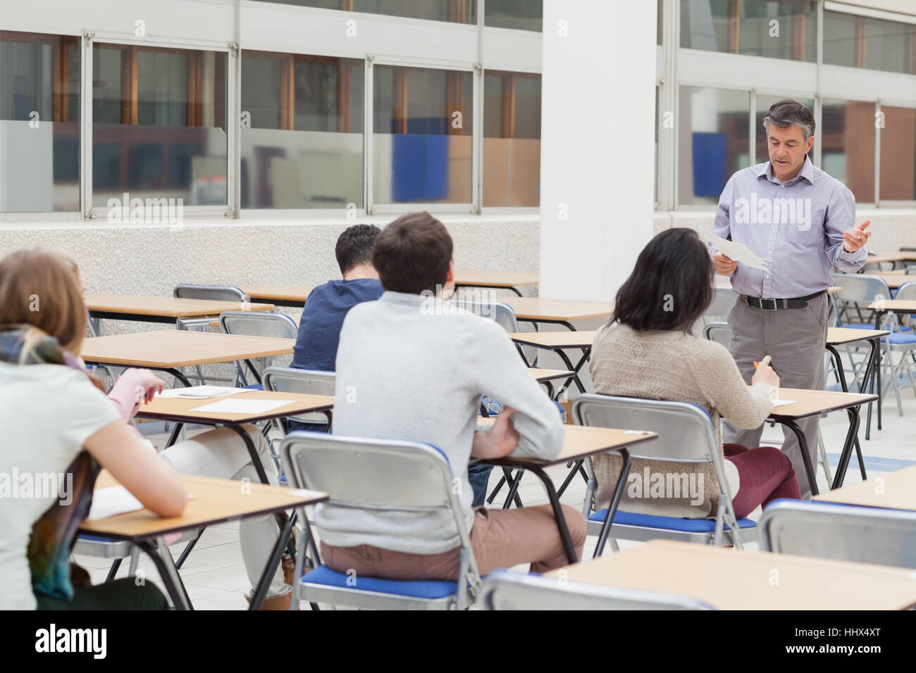 Lecturer talking at top of class in college - Stock Image