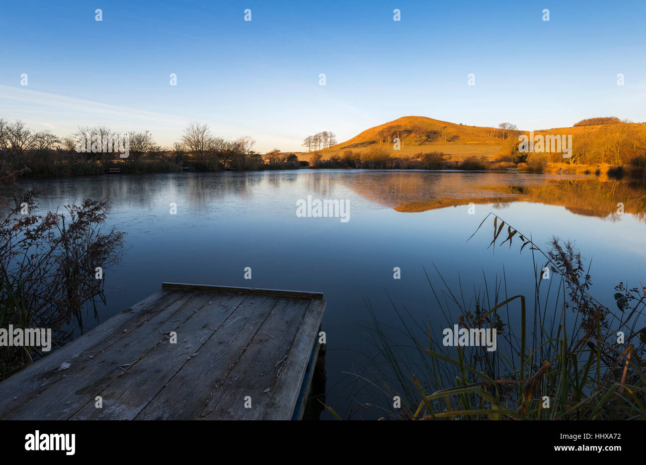 Summerhouse Hill on the Kent Downs reflected in Beachborough ponds at dawn. - Stock Image