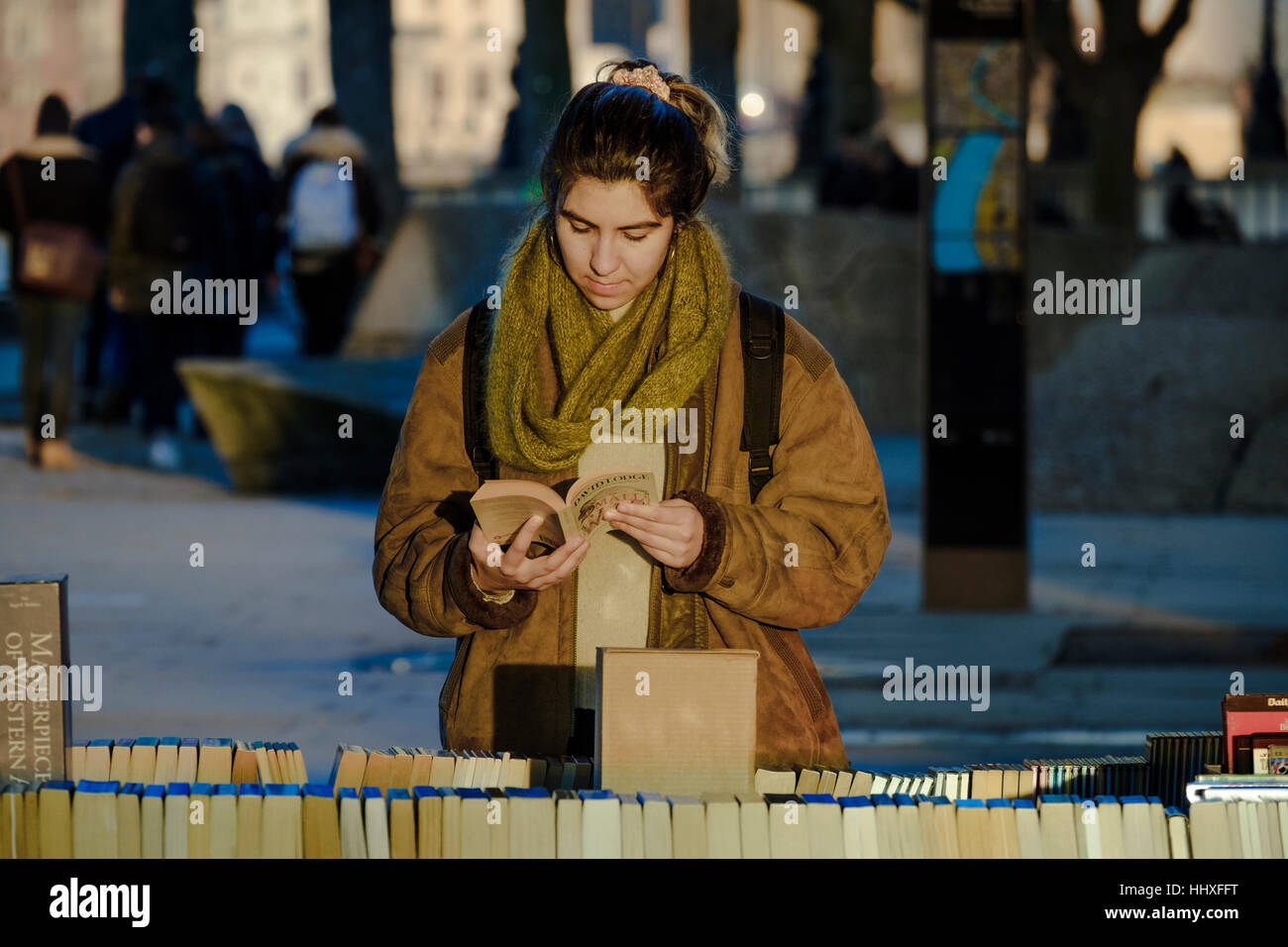 Young woman at second-hand bookstall beneath Waterloo Bridge, South Bank, London, UK - Stock Image