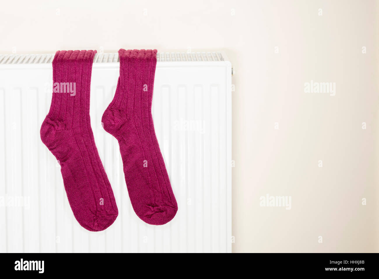 A pair of hiking socks hanging over a radiator. - Stock Image