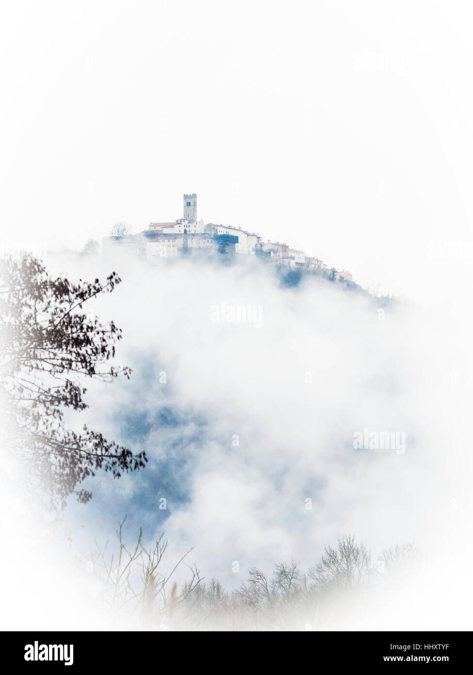 Motovun old town in Istria in Croatia atop above fog clouds artistic arty view vertical distant view landscape Stock Photo
