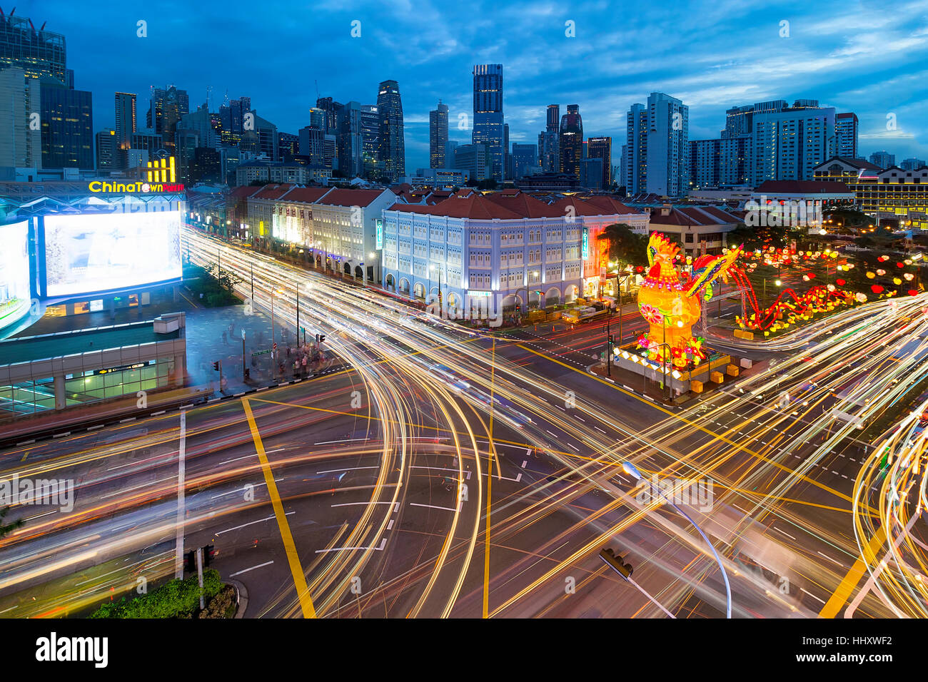Rush Hour Traffic Light Trails at Singapore Chinatown with Chinese New Year of the Rooster decoration - Stock Image