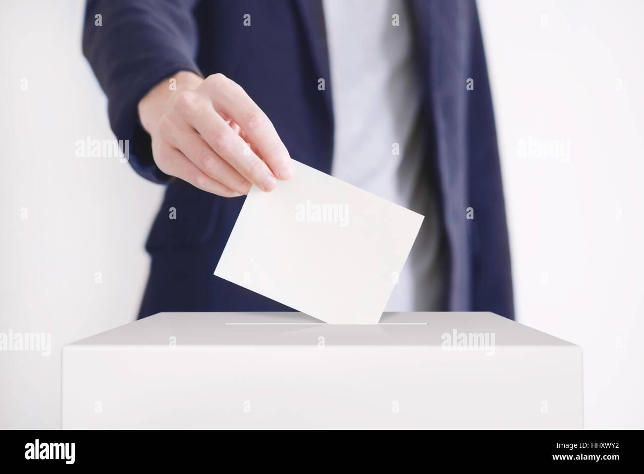 Man putting a ballot into a voting box. - Stock Image