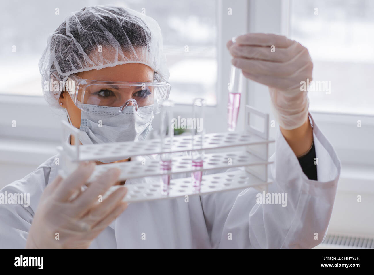 Serious female chemist working in laboratory - Stock Image