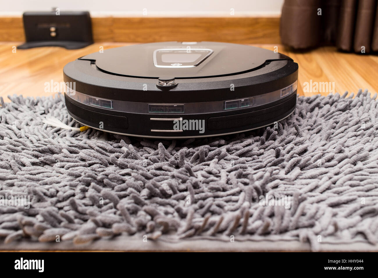 Robotic vacuum cleaner on wood parquet floor, Smart vacuum, new automate technology housework - Cleaning on carpet. - Stock Image
