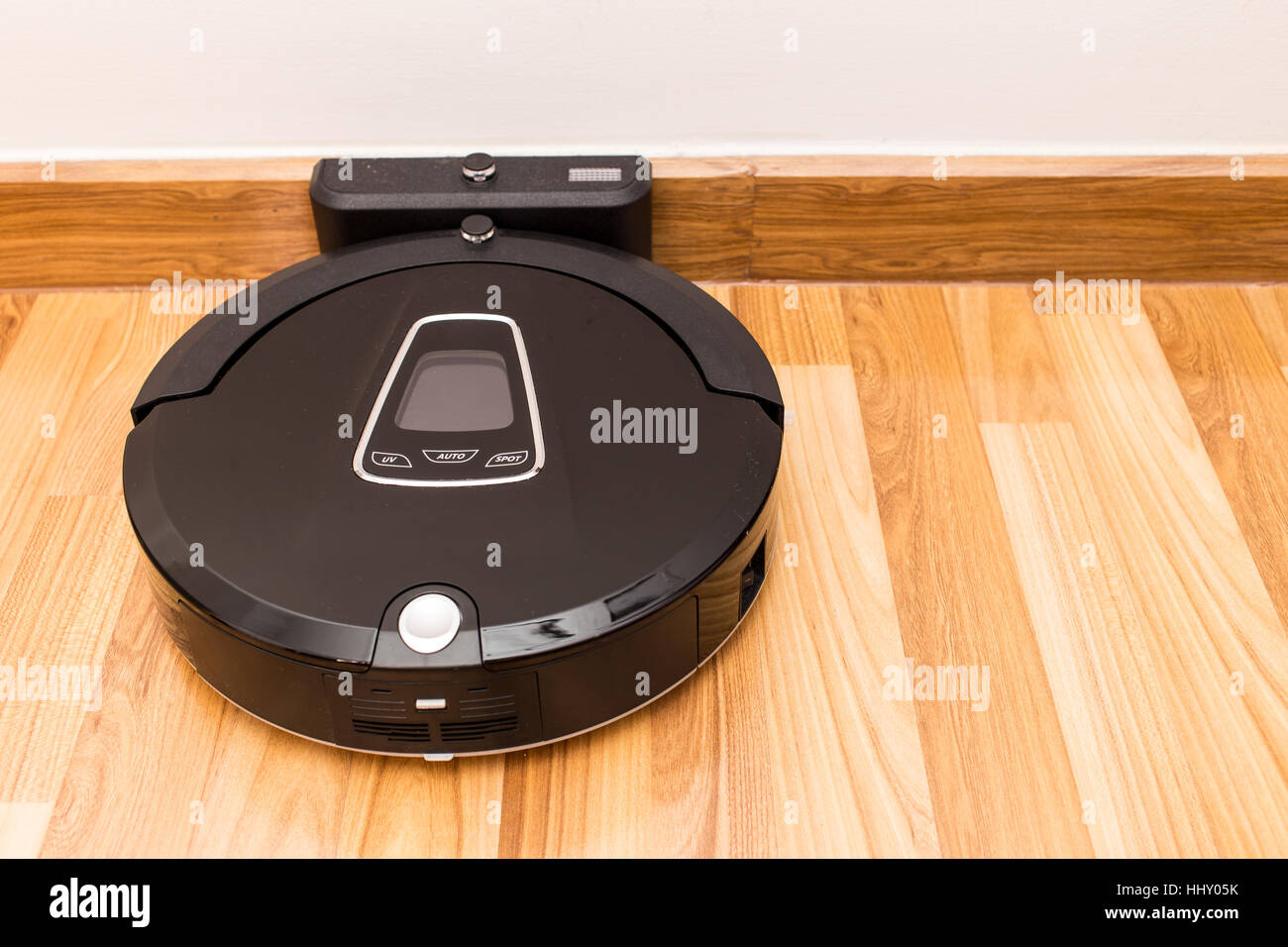 Robotic vacuum cleaner on wood parquet floor, Smart vacuum, new automate technology housework. - Stock Image
