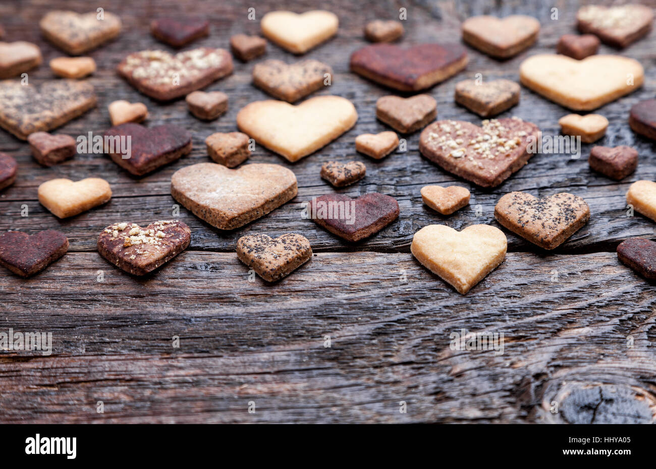 Delicious heart shaped cookies baked with love on wooden background - Stock Image