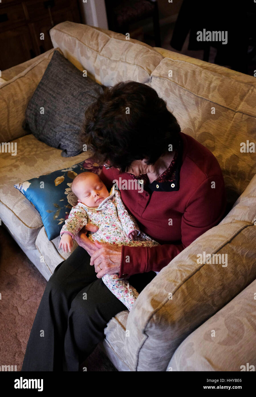 Elderly woman in her eighties cradling a young baby girl in her arms - Stock Image