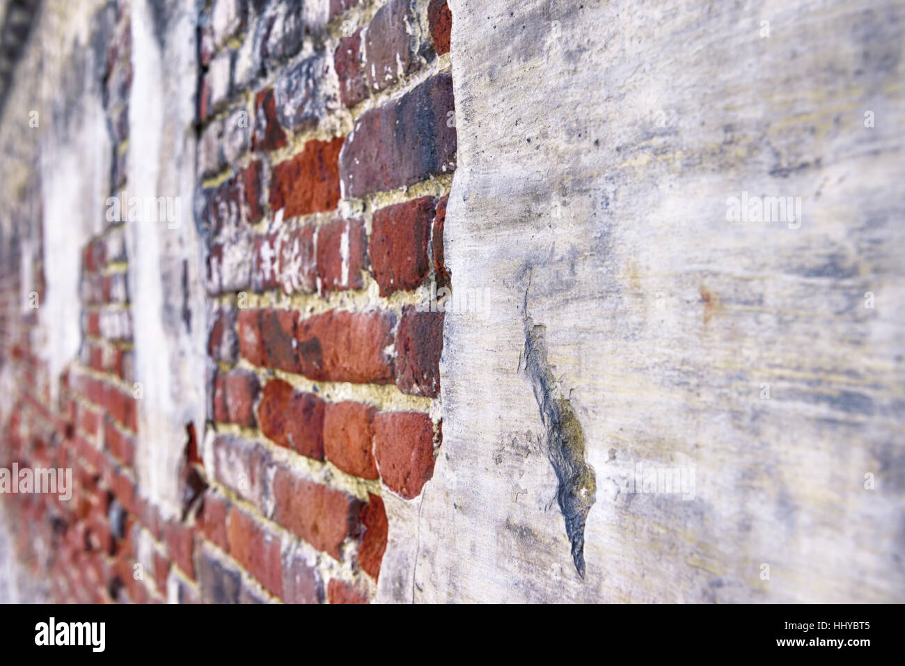 Very old street fence wall built from red bricks and painted - Stock Image