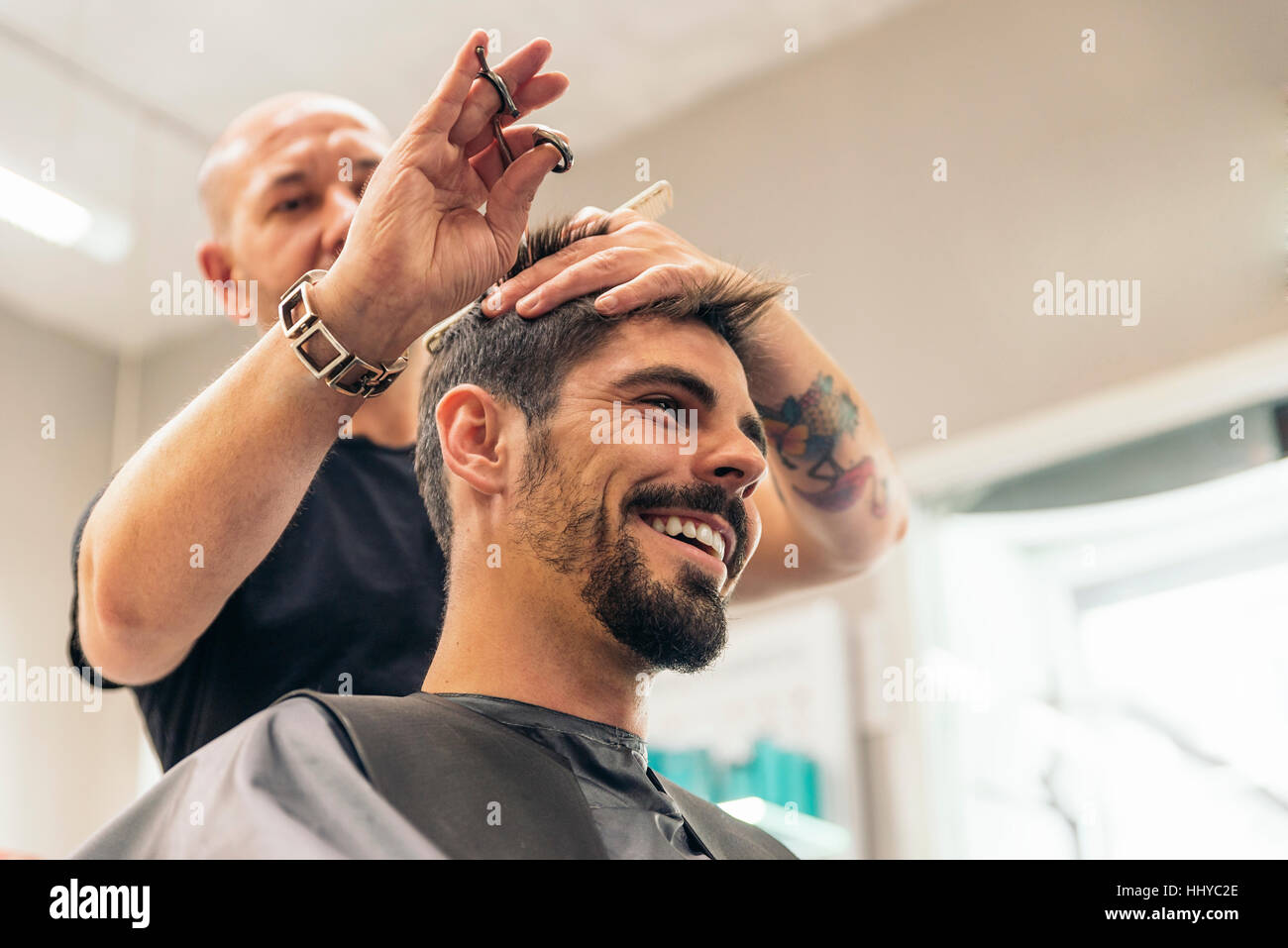 Hairstylist making men's haircut to an attractive man in the beauty salon. - Stock Image