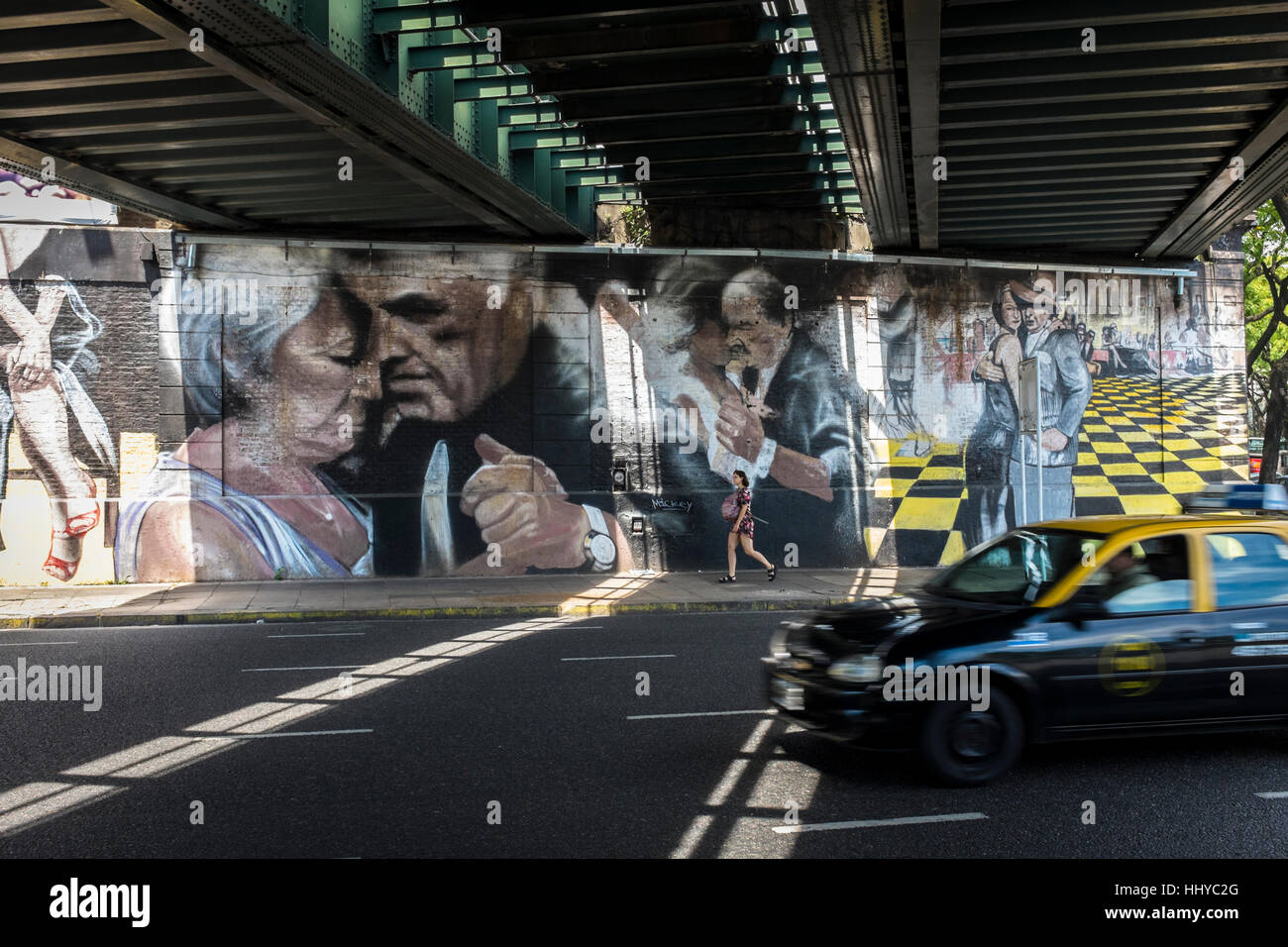 A taxi drives under a railway bridge where painted walls depict three couples dancing Tango in Buenos Aires city, - Stock Image