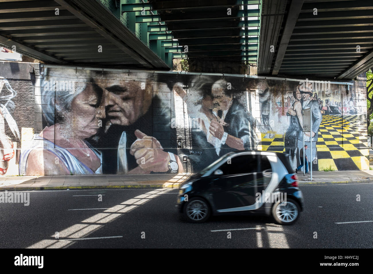 A car drives under a railway bridge where painted walls depict three couples dancing Tango in Buenos Aires city, - Stock Image