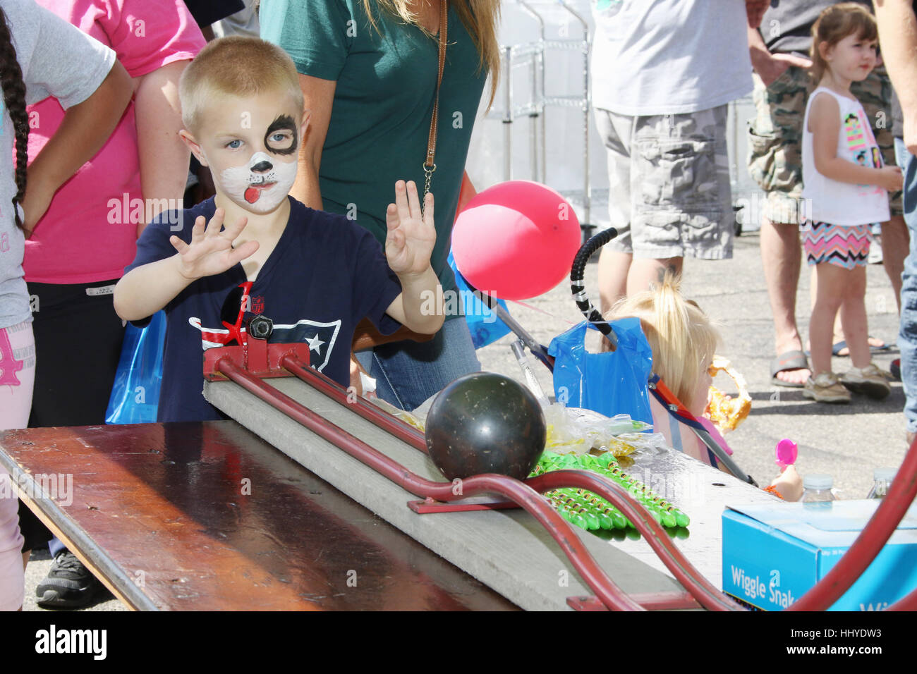 Young boy with face paint rolls a ball down a track in a Roller Bowler carnival game. Beavercreek Popcorn Festival. - Stock Image