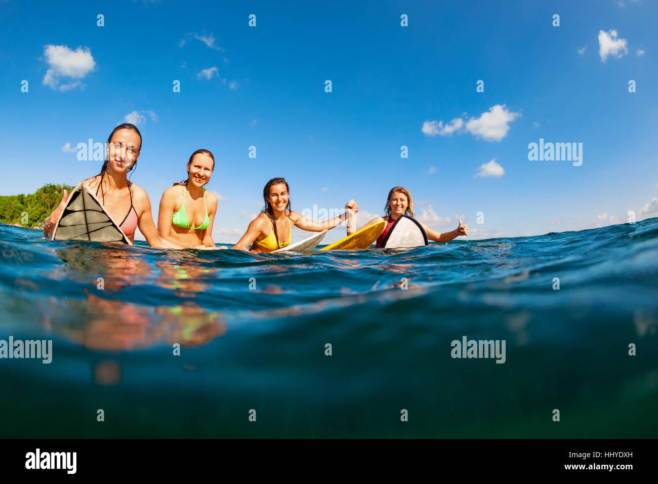 Girls in bikini - group of surfers on surf boards, women wait for ocean wave People in water sport adventure camp, - Stock Image