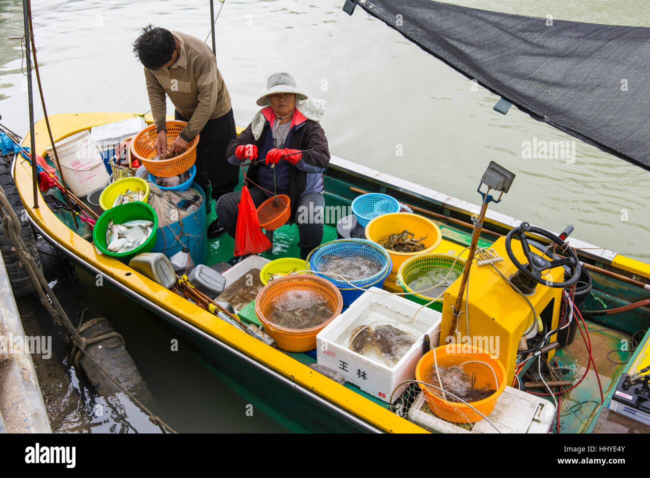 while fishermen sell the fish on their boat in the village of Tai O, Hong Kong - Stock Image