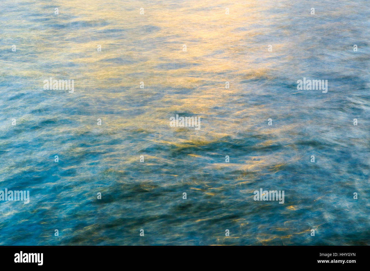 Abstract golden light reflecting on blue water - Stock Image