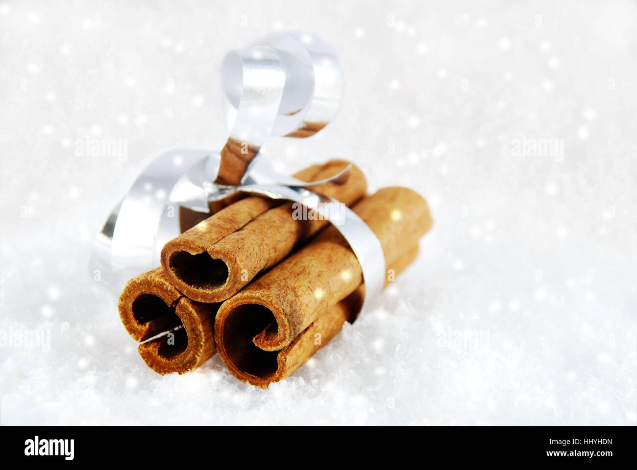cinnamon sticks as a present in the snow with white snowflakes - Stock Image