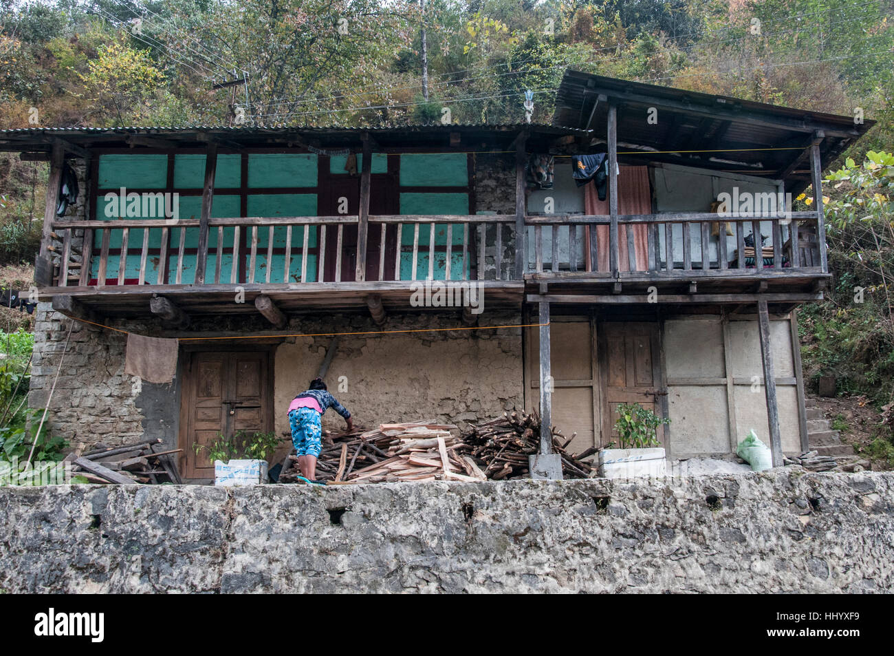 A householder tidying her front porch beside the Tawang road, Arunachal Pradesh, northeast India - Stock Image