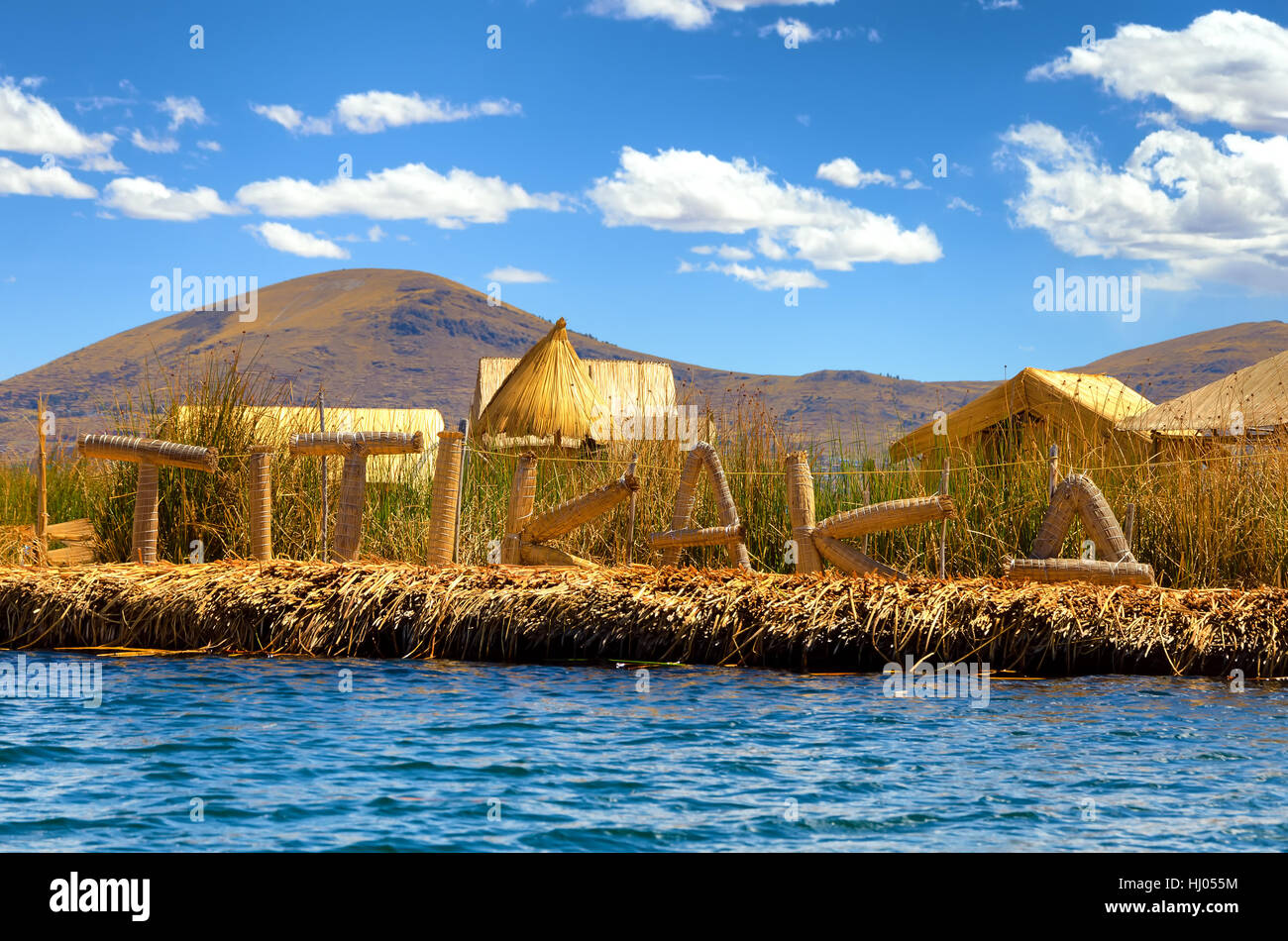 Manmade floating island with a sign spelling out Titikaka on Lake Titicaca in Peru - Stock Image