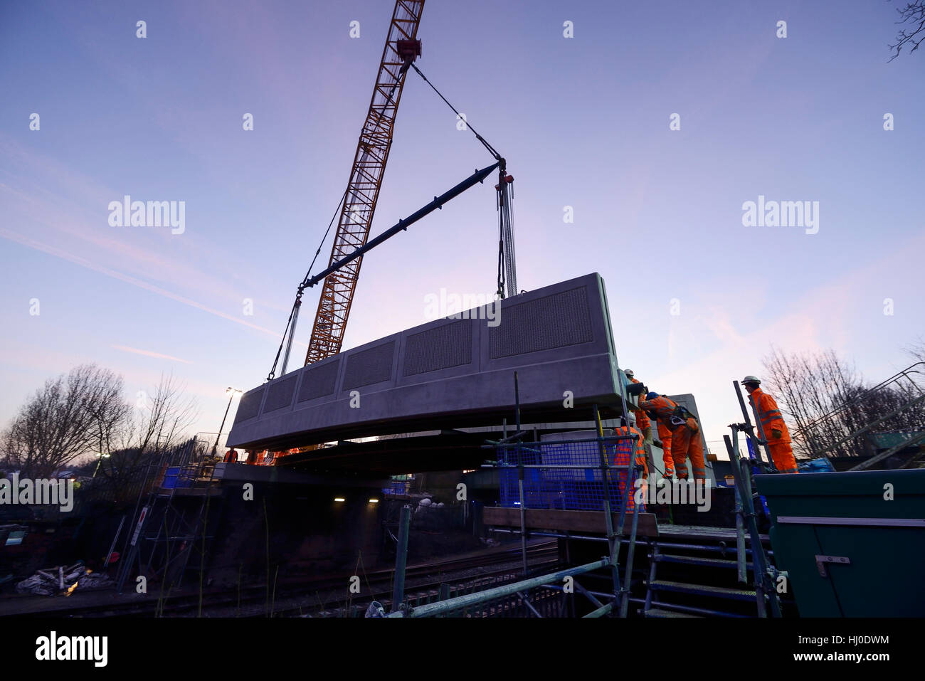 Chester, UK. 21st January 2017. Installation of a concrete road bridge at first light on Brook Lane over the Merseyrail - Stock Image
