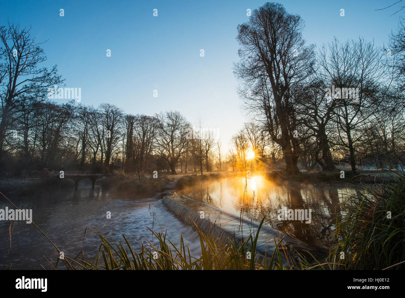 Morden Hall Park, London, UK. 21st January, 2017. Mist rising from a weir on the river Wandle as the sun rises on Stock Photo