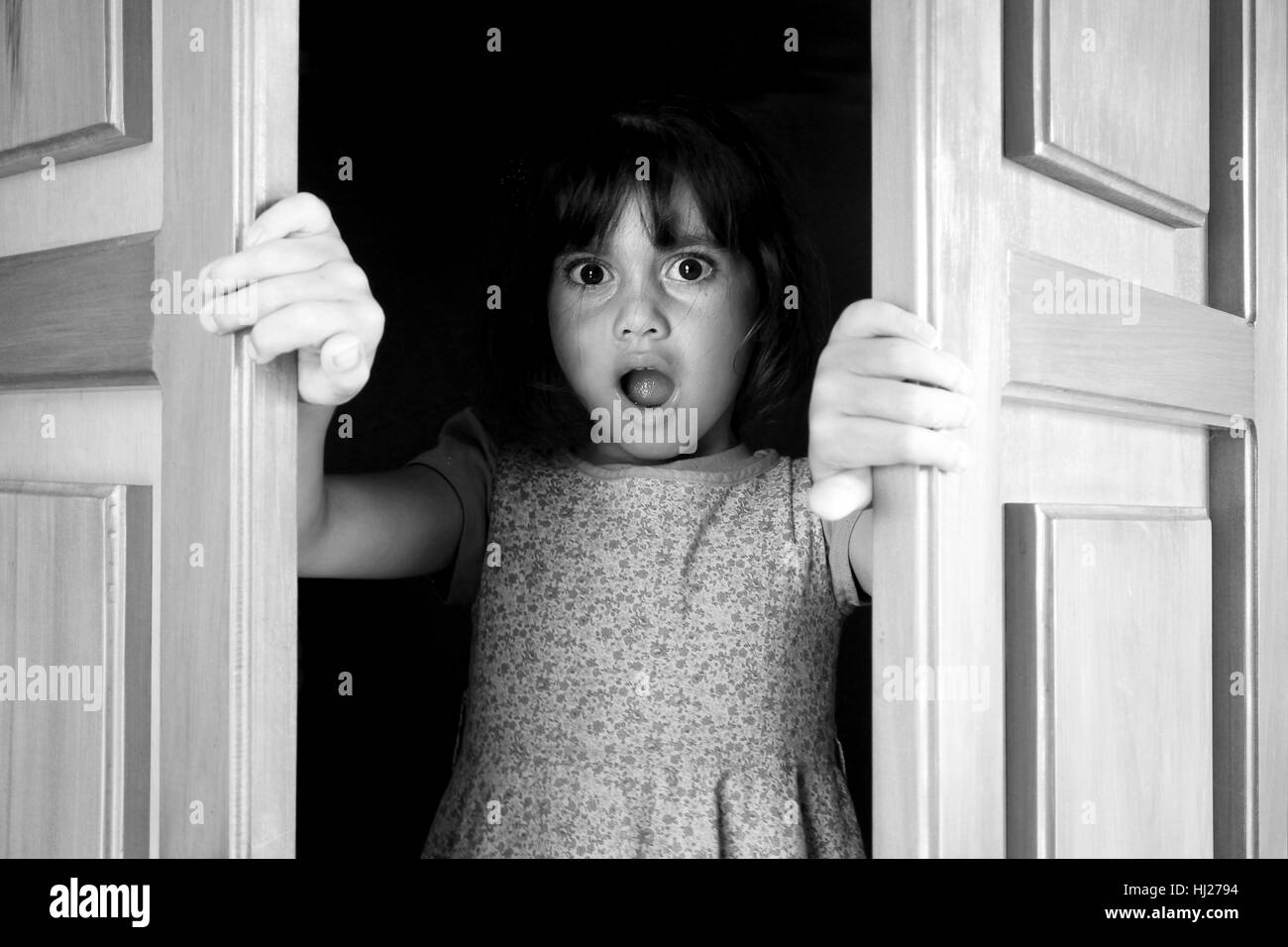 Young girl (age 6-7)surprised to find and see what is behind closed doors. Children childhood concept. Real people - Stock Image