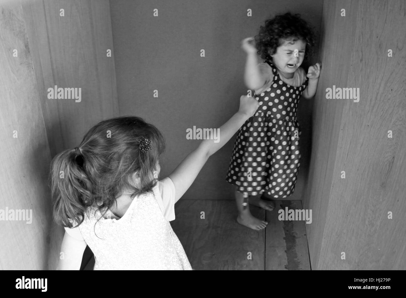 Young sister girls (age 7 and 3) fighting at home. Children childhood concept. Real people copy space (BW) - Stock Image