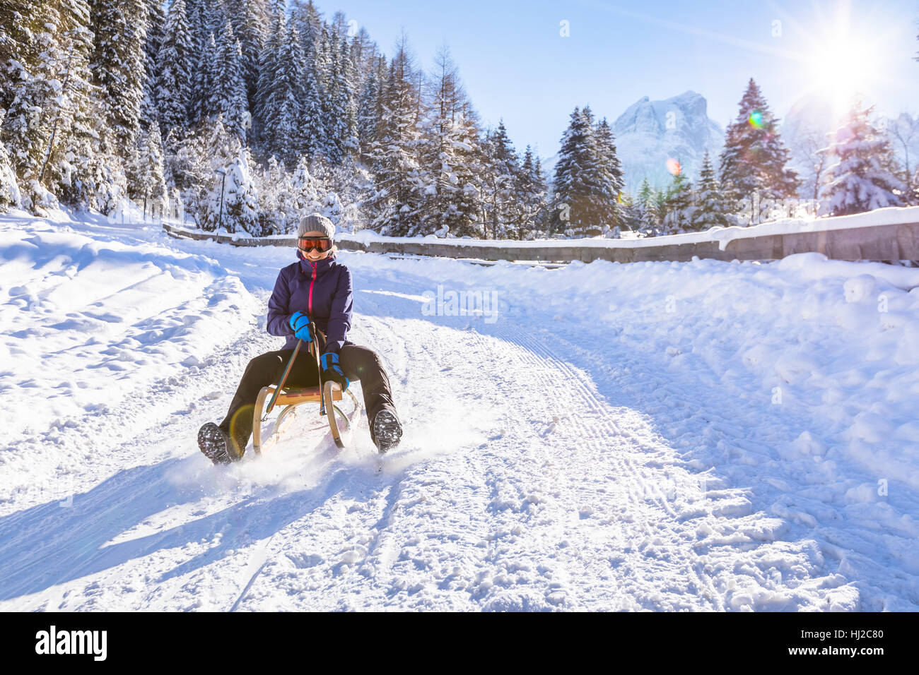 Cheerful girl riding a sled downhill on a snow covered sledge trail in a white sunny winter mountain landscape - Stock Image