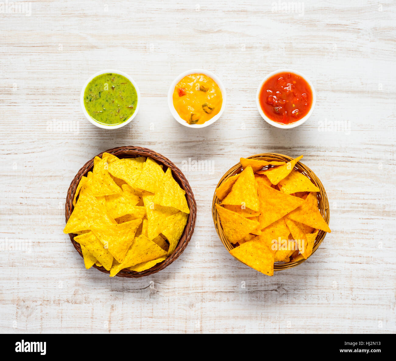 Mexican Cuisine Appetizer Tortilla Corn Chips with Guacamole, Chese and Tomato dip in Top View - Stock Image