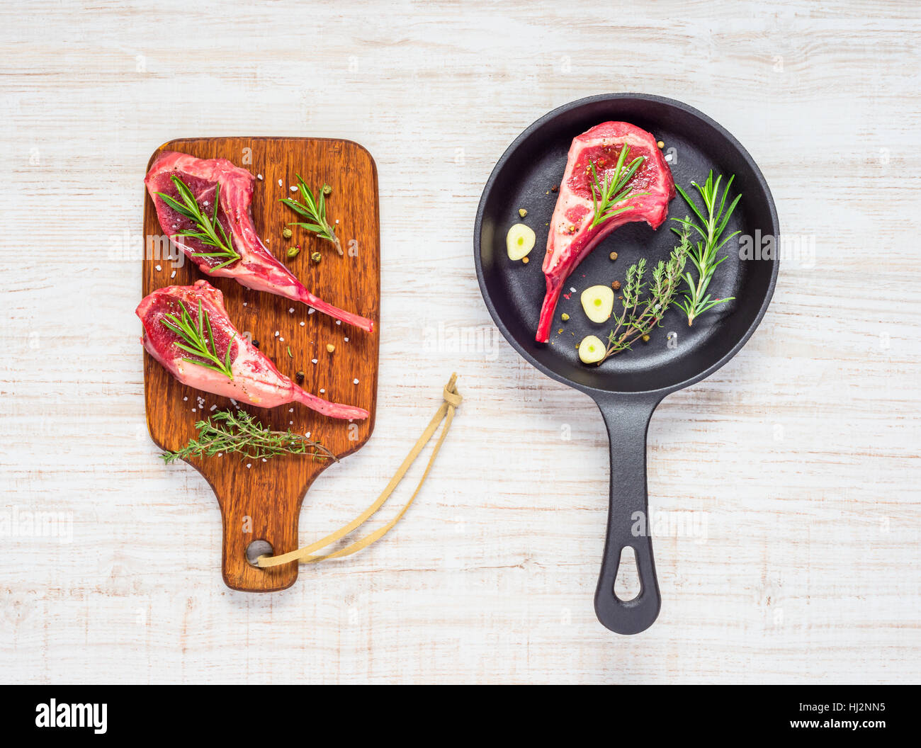 Lamb Chops Ribs Meat in Frying Pan and on Wooden Chopping Board in Top View Stock Photo