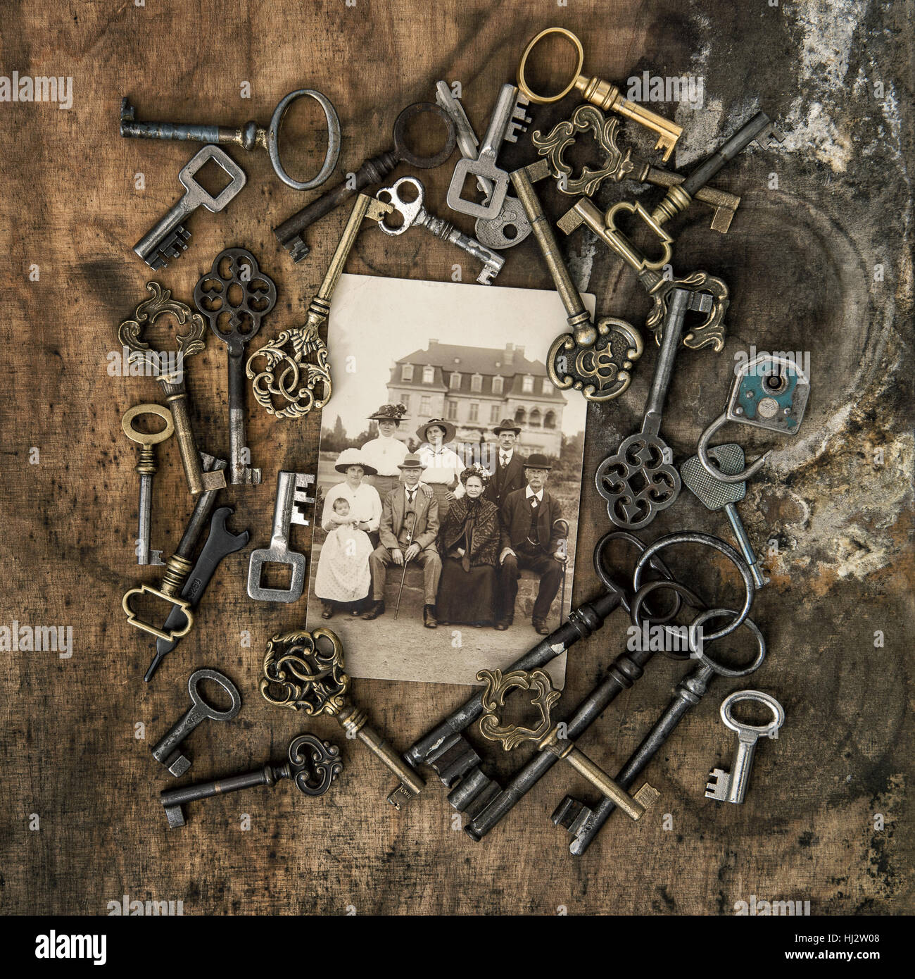 Vintage photo family portrait with house on background. Old keys over wooden texture Stock Photo