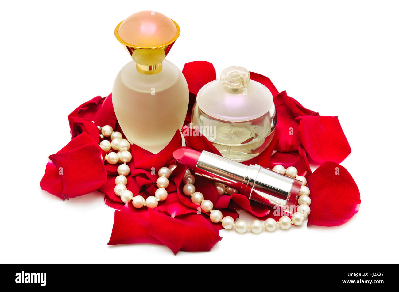 Perfume and pearl necklace in rose petals isolated on white. - Stock Image
