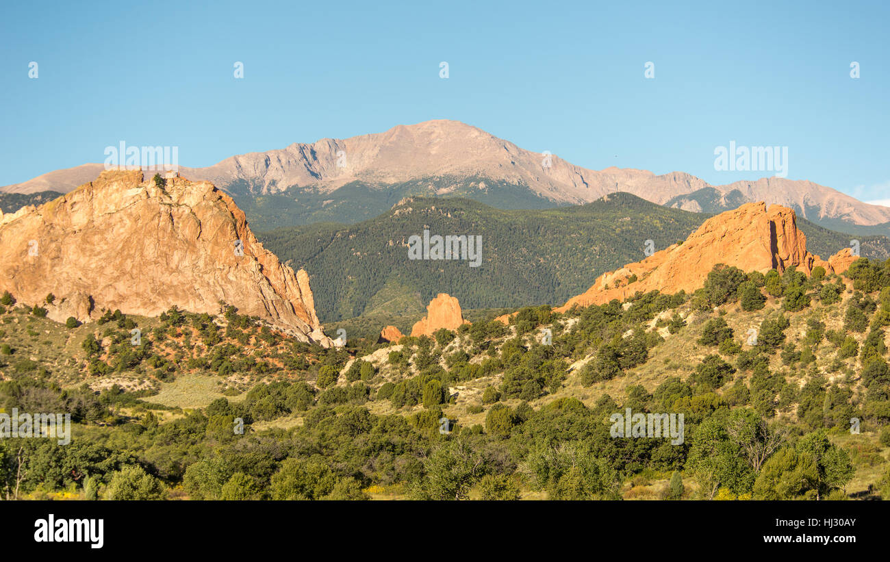 Morning light illuminates Pikes Peak, towering over South Gateway, North Gateway, Kissing Camels, and the Tower - Stock Image