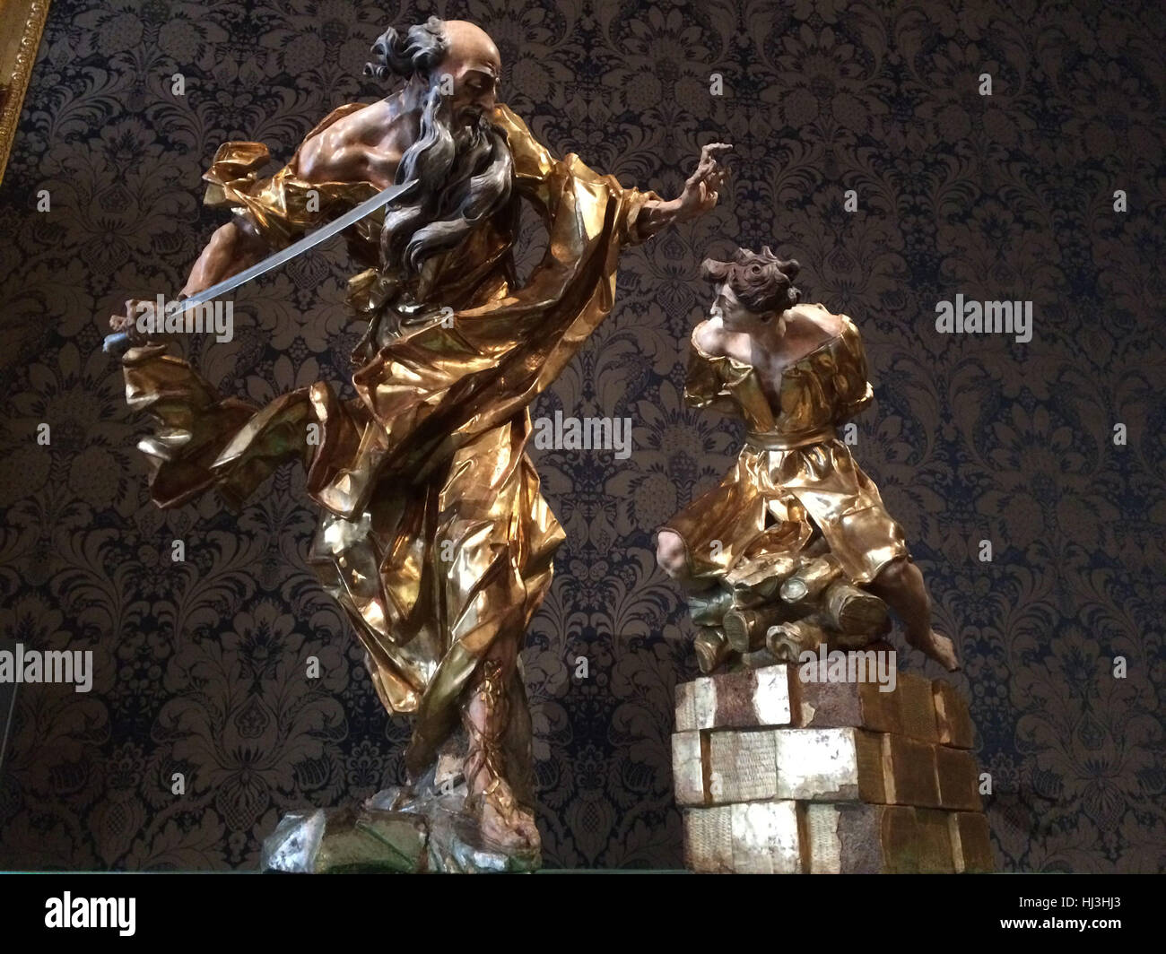 Sacrifice of Isaac (1758). Gilded and coloured wooden statue by Baroque sculptor Johann Georg Pinsel on display - Stock Image