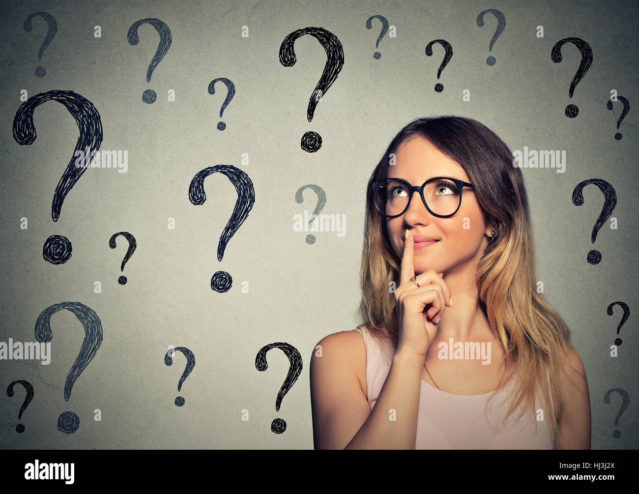 Thinking business woman with glasses looking up at many questions mark isolated on gray wall background Stock Photo