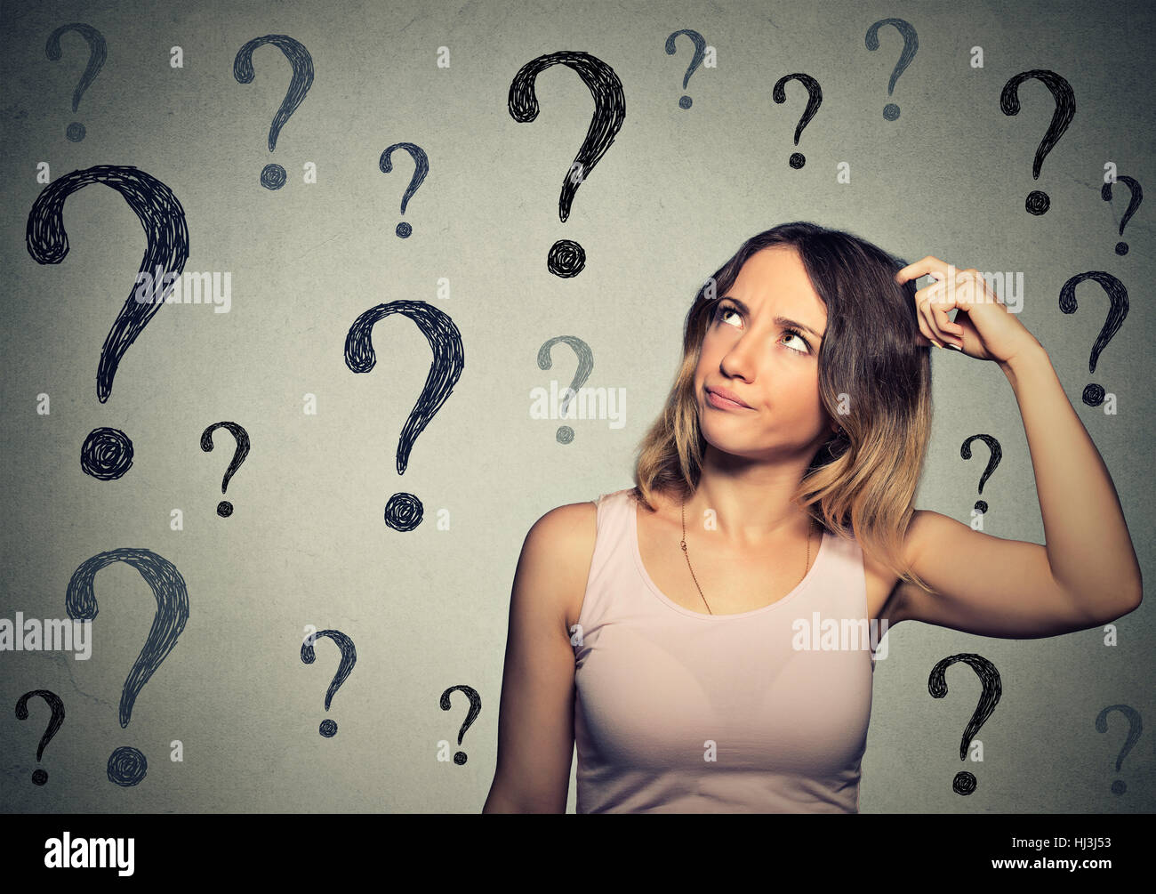 Thinking young woman with looking up at many questions mark isolated on gray wall background - Stock Image
