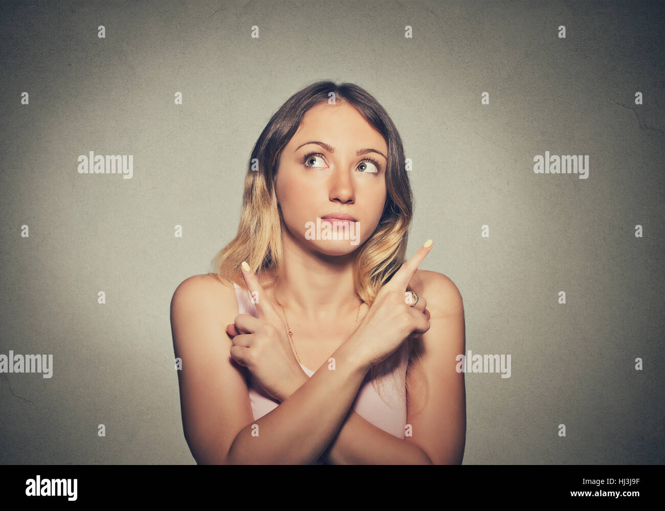 Confused thinking woman isolated on gray wall background - Stock Image